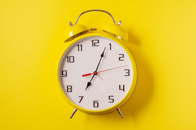 Yellow illuminating color retro style alarm clock on yellow
