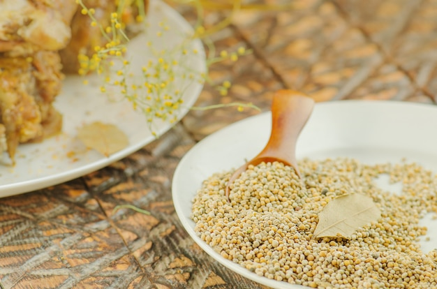 Yellow indian mustard seed in white bowl