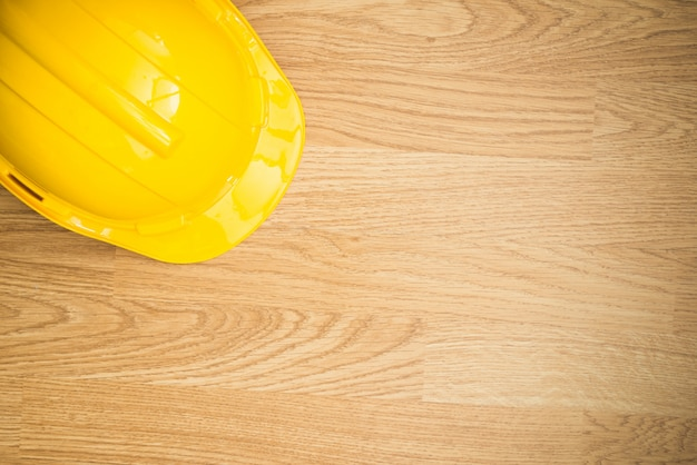 Yellow industrial protective helmet on wooden background