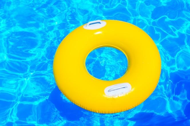 Желтый надувной детский круг в бассейне