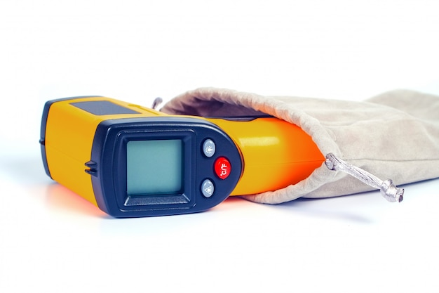 Yellow infrared thermometer gun used to measure temperature  on white.