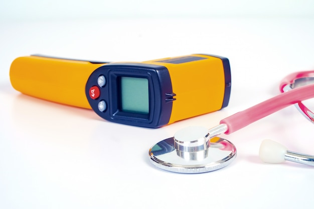 Yellow infrared thermometer gun used to measure temperature with stethtoscope  on white.