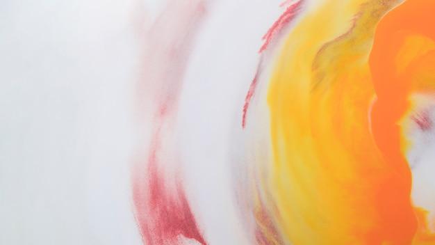 흰 거품 배경에서 녹는 노란 잉크