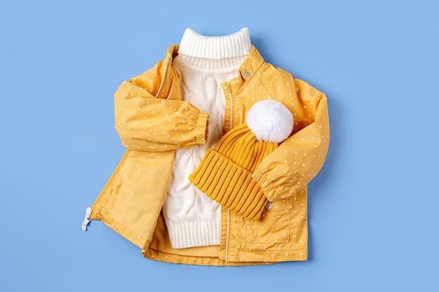 파란색 배경에 노란색 재킷과 따뜻한 스웨터와 모자. 가을이나 겨울을 위한 아동복 세트. 패션 아동복.