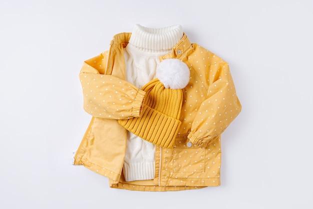 흰색 바탕에 노란색 재킷과 따뜻한 스웨터와 모자. 가을이나 겨울을 위한 아동복 세트. 패션 아동복.