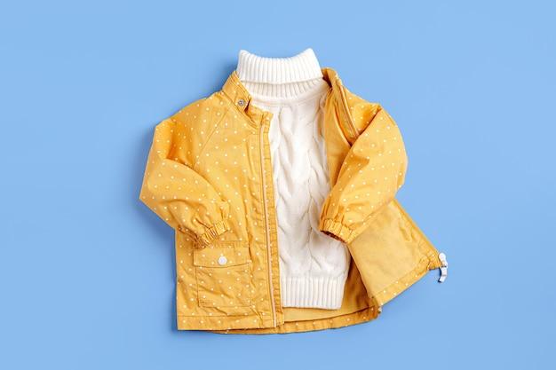 파란색 배경에 노란색 재킷과 따뜻한 스웨터. 가을 아동복 세트입니다. 패션 아동복.