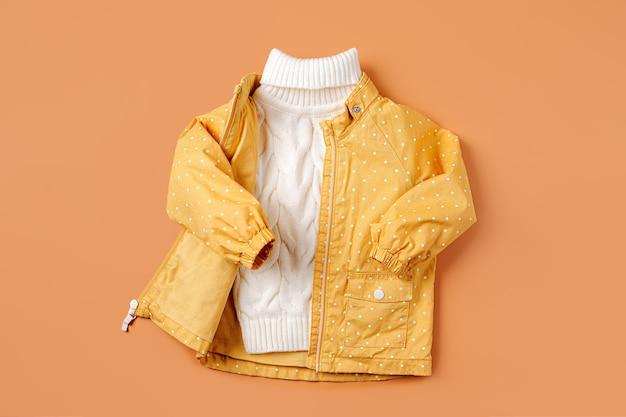 주황색 배경에 노란색 재킷과 따뜻한 스웨터. 가을 아동복 세트입니다. 패션 아동복.