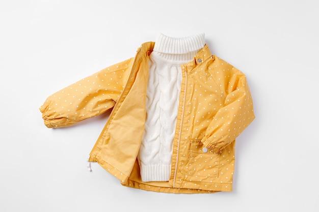 흰색 바탕에 노란색 재킷과 따뜻한 스웨터. 가을 아동복 세트입니다. 패션 아동복.
