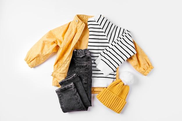 흰색 바탕에 노란색 재킷, 청바지, 점퍼. 가을 아동복 세트입니다. 패션 아동복.