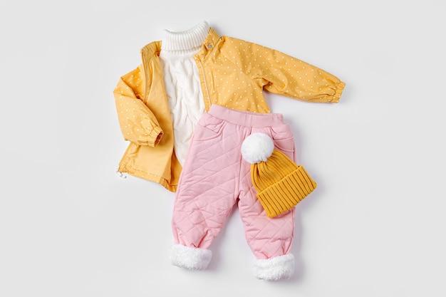 흰색 바탕에 노란색 재킷, 따뜻한 바지, 모자. 겨울용 아기 옷 세트입니다. 패션 아동복.