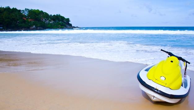 Желтый водный мотоцикл на пляже - лето