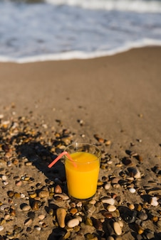 Yellow juice in glass with red drinking straw near seashore at beach
