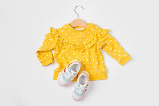 スニーカーとハンガーの黄色いジャンパー。白地に春、秋、夏のベビー服とアクセサリーのセットです。ファッションキッズ衣装。フラットレイ、上面図