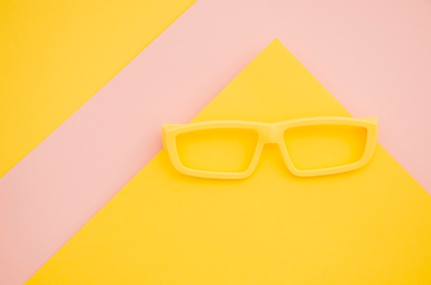 Yellow kids eyeglasses on pink and yellow background