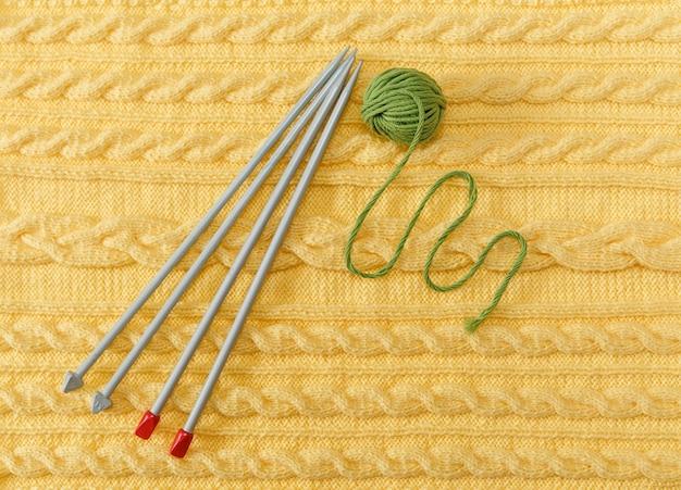 パターンと三つ編みの黄色のニットの背景灰色の編み針