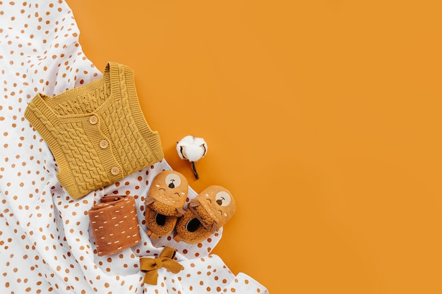 Желтый вязаный комбинезон, носки и милые детские тапочки с муслиновым пеленальным пледом. комплект одежды и аксессуаров для новорожденных. плоская планировка, вид сверху