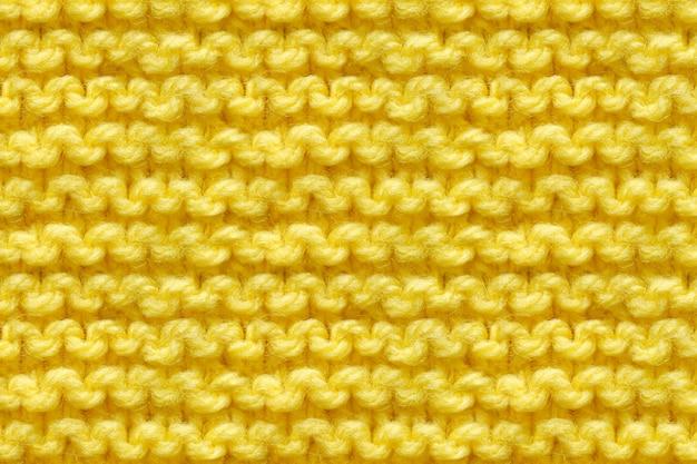 노란색 니트 원단 질감입니다. 뜨개질 텍스처 매크로 스냅 샷. 뜬