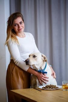 Желтый лабрадор-ретривер сидит за столом со своей хозяйкой. корм для собак в белой тарелке, друг собака Premium Фотографии