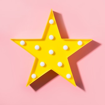 Yellow lamp as star with white led lights on pink background.