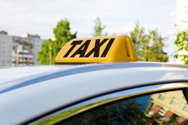 Желтая лампа со словом такси на крыше автомобиля