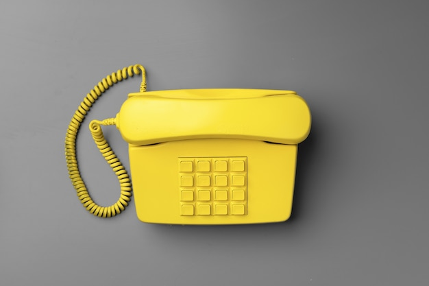 Yellow .landline phone on gray background