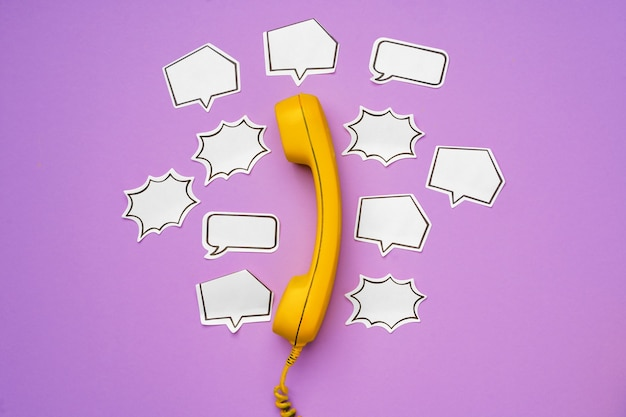 紫色の吹き出し付きの黄色の固定電話
