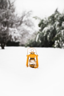 Yellow lantern on snow