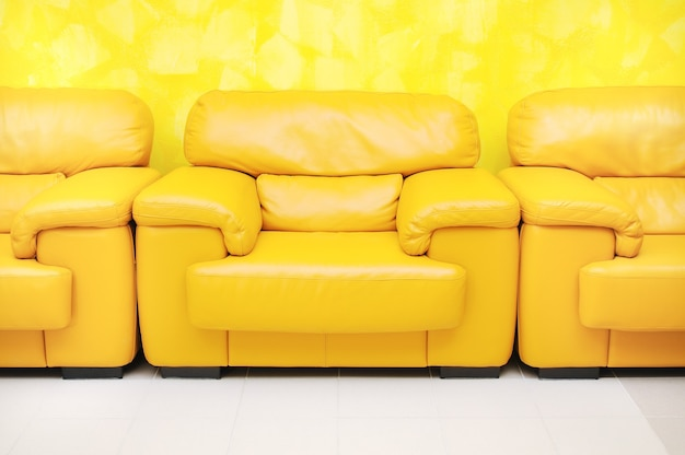 Yellow leather armchairs in waiting room and yellow textured wall