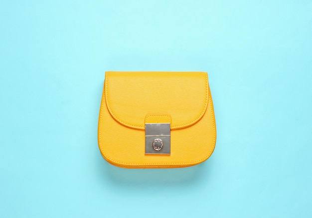 Yellow leather mini bag on blue surface