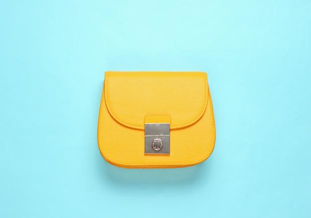 Желтая кожаная мини сумка на синей поверхности