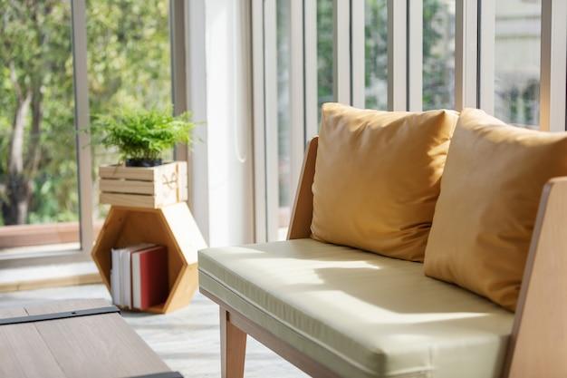Yellow leather pillow on sofa near the window