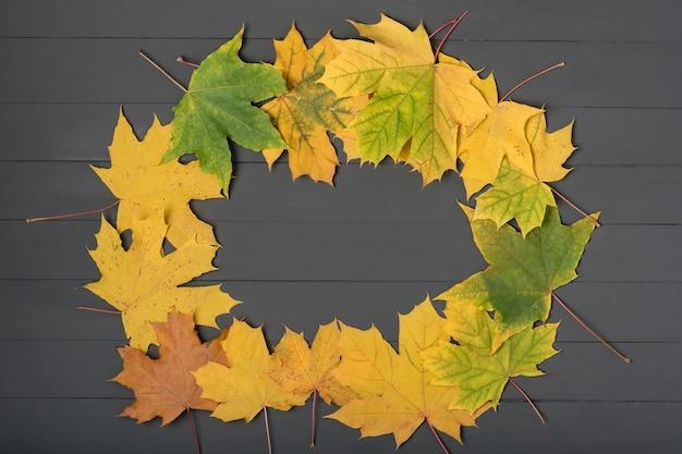 Желтые листья, сложенные в форме рамки на сером деревянном фоне. шаблон. фон. макет.