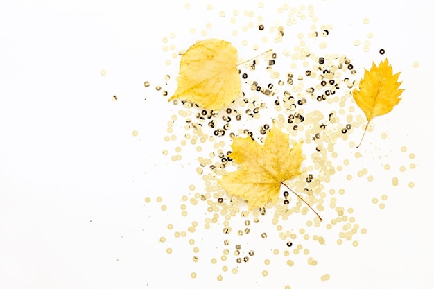 Yellow leaves and golden sparkles on white background. autumn holiday concept.
