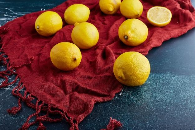 赤いタオルの上の青い背景に黄色いレモンとスライス。