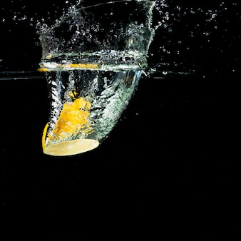 Yellow lemon falling into water splash