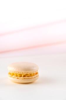 Желтые лимонные французские миндальное печенье или миндальное печенье на белом и розовом фоне