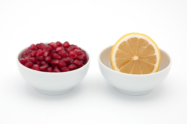 Yellow lemon and red seeds of pomegranate in cups on a white background.