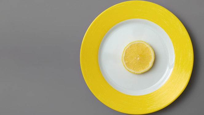 궁극적 인 회색 표면에 노란색 접시에 노란색 레몬 슬라이스. 2021 년 올해의 색상. 일루미 네이 팅 및 얼티밋 그레이. 평평하다.