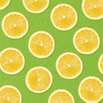 Yellow lemon slices on green background closeup studio photography