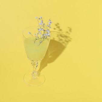 Желтый лимонадный напиток на желтом фоне с цветами в стекле. монохромные цвета. концепция летней вечеринки