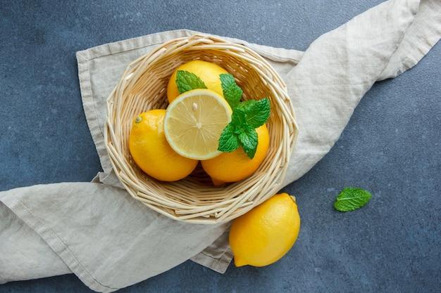 暗い表面の白い布の上面図のバスケットに黄色いレモンと葉