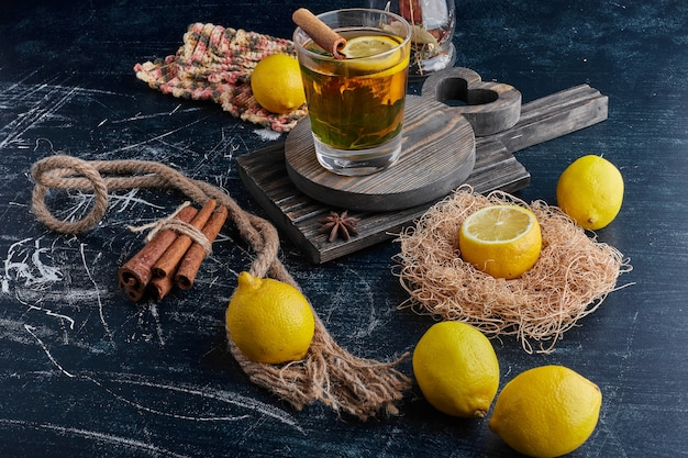 Limoni gialli su una superficie nera con un bicchiere di vino scintillante.
