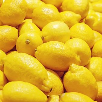 イエローレモンは果物市場、明るいレモン背景でクローズアップ