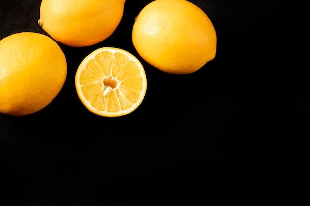 Желтые лимоны. рамка из лимонов на черном фоне с пространством для подписи. витамин с.