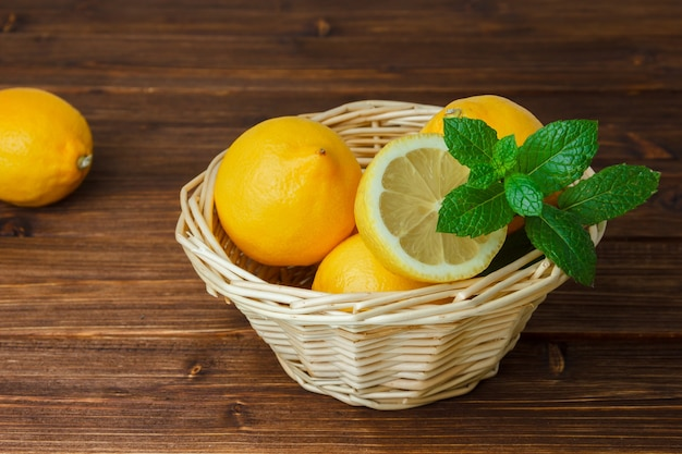 Yellow lemons and green leaves in a basket with sliced lemon high angle view on a wooden surface
