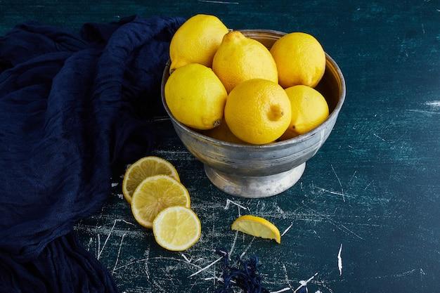 Желтые лимоны в металлической чашке.