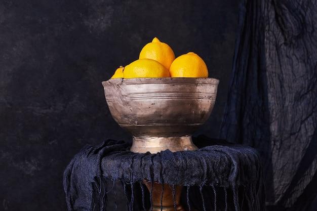 Yellow lemons in a metallic ethnic bowl.