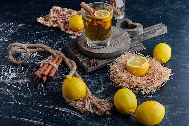 Желтые лимоны на черной поверхности с бокалом блестящего вина.