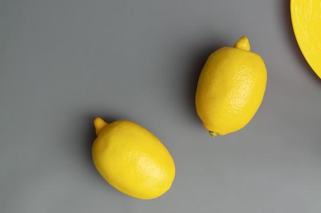 Желтые лимоны на сером фоне