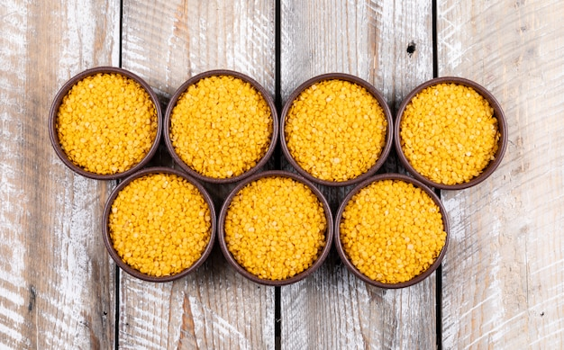 Yellow lentils in a brown bowls on a beige wooden table. top view.
